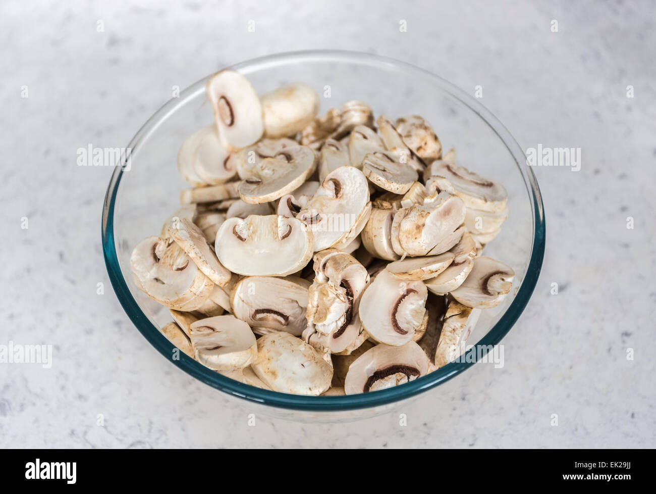 Home cookery ingredients - a glass or Pyrex bowl of raw, uncooked prepared sliced button mushrooms ready for use - Stock Image