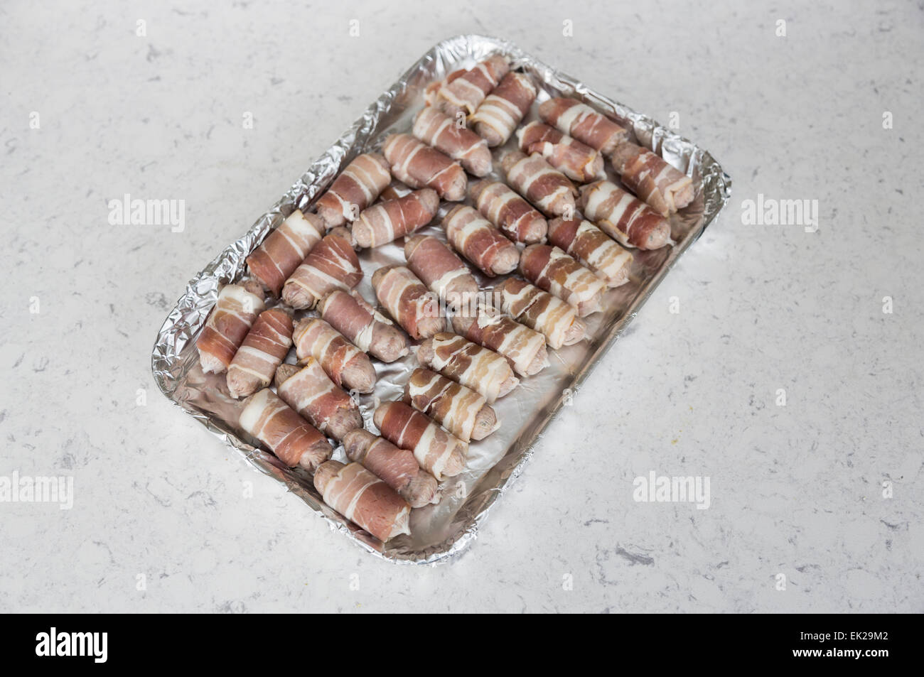 Tray lined in foil with uncooked small sausages wrapped in bacon (pigs in blankets) ready for cooking, part of a - Stock Image