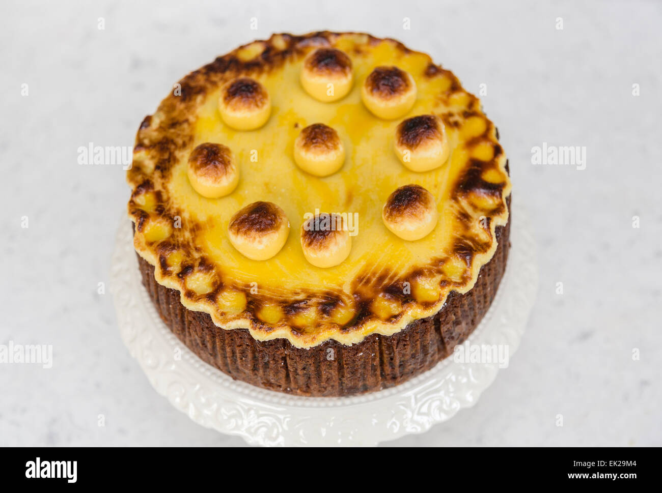 Traditional home baked simnel cake on a white china cake stand for Easter - fruit cake with toasted marzipan topping - Stock Image