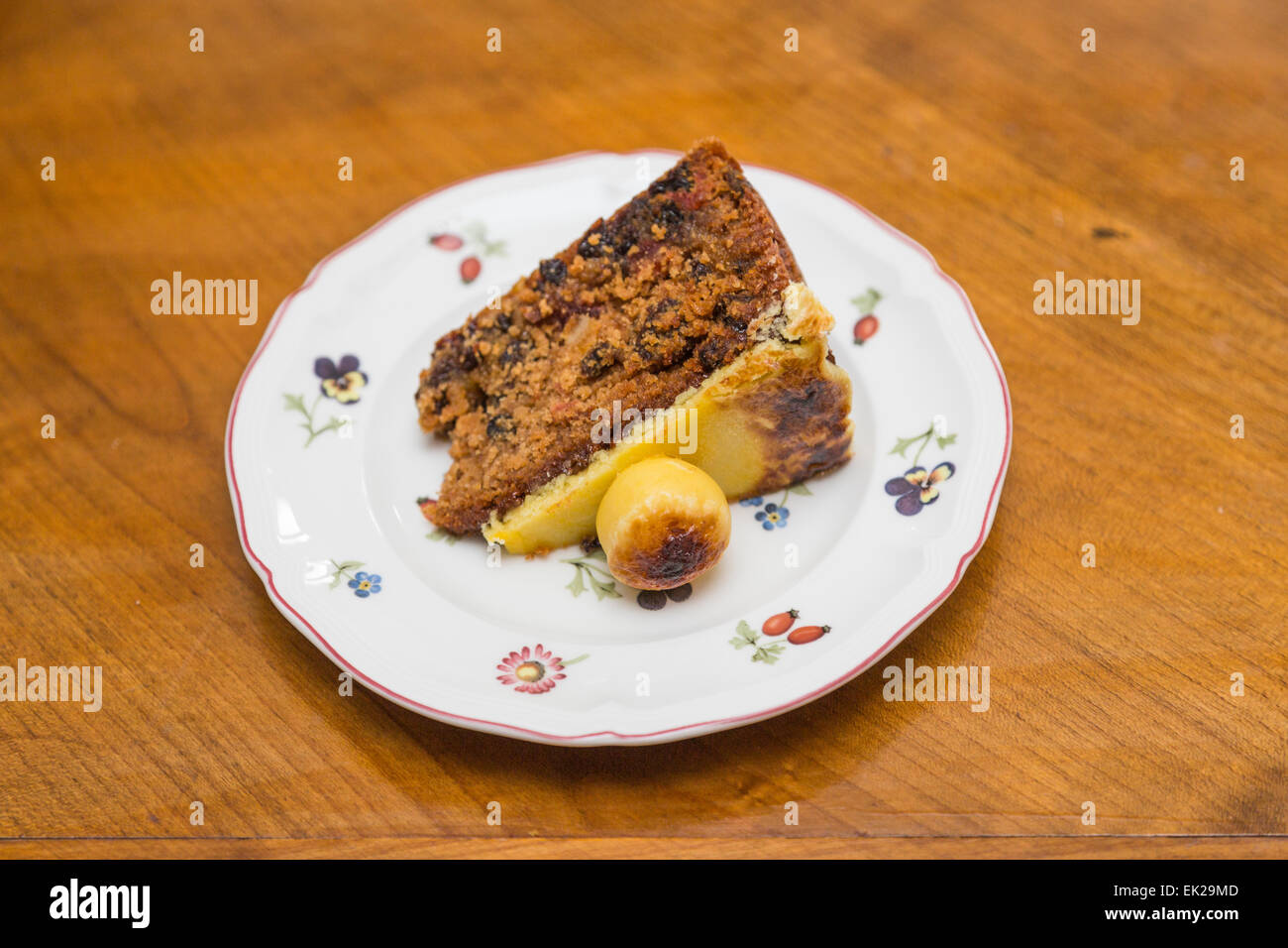 Slice of traditional Easter simnel cake, a fruit cale with marzipan topping and ball served on a flowery white china Stock Photo