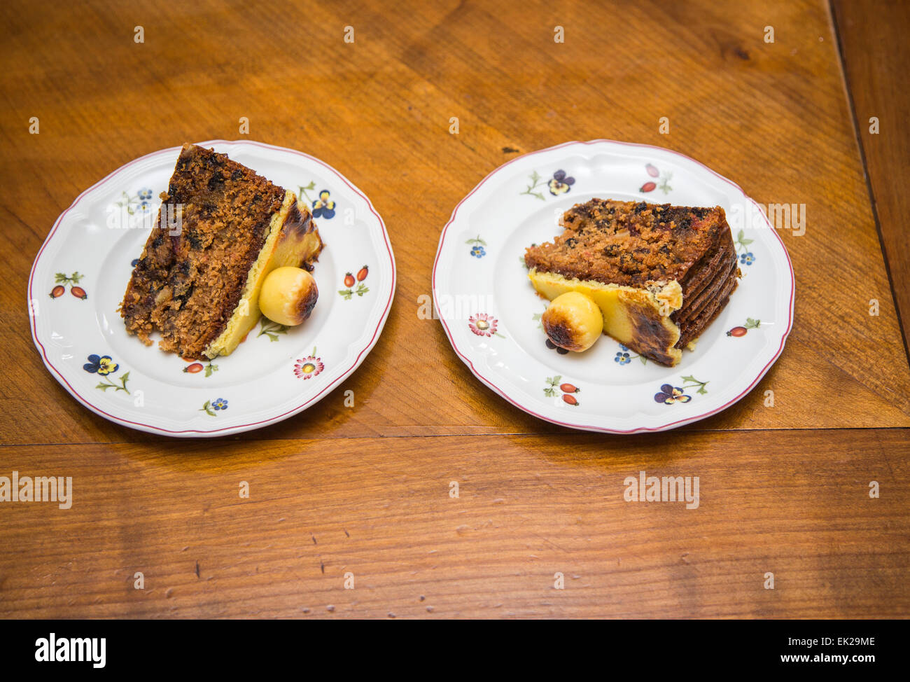 Two slices of traditional Easter simnel cake, a fruit cake with marzipan topping and balls served on flowery white Stock Photo