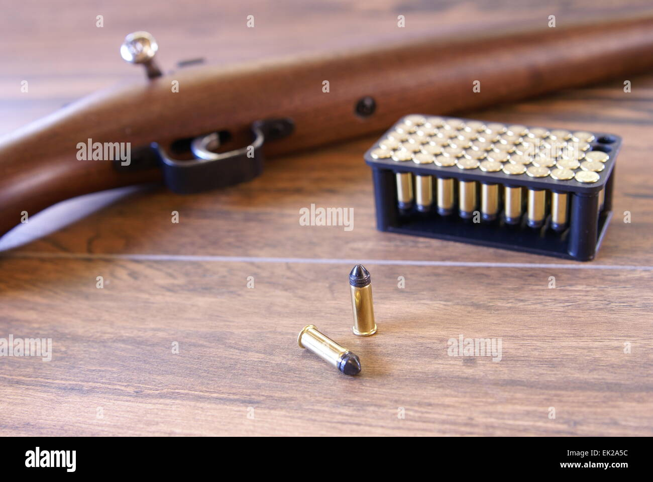 simple hunting rifle with ammunition laying beside it wooden stock