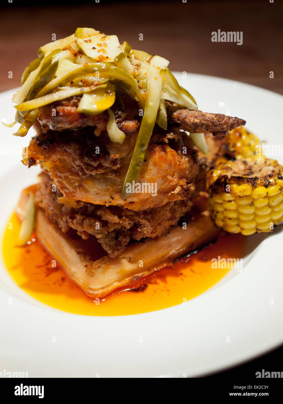 Soul food: a gourmet chicken and waffle dish topped with dill pickles from Bon Temps Cafe in Saskatoon, Saskatchewan, - Stock Image