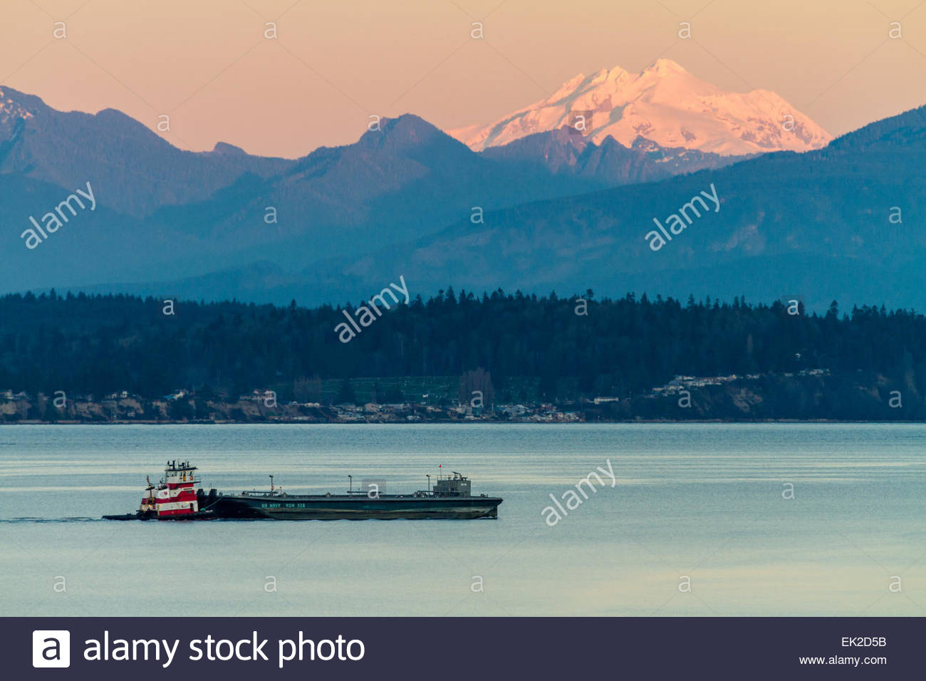 View of US Navy ship with mountains in background at sunrise Stock Photo