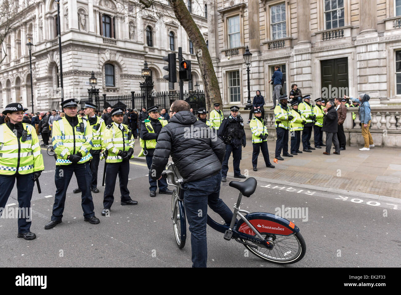 A cyclist attempting to ride through a police cordon in Whitehall. Stock Photo