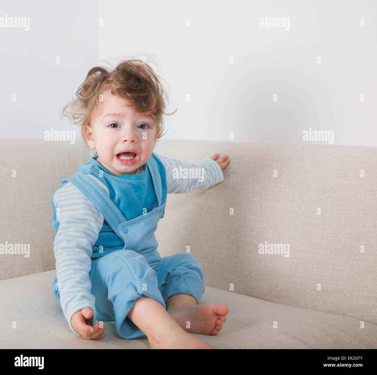 1 year old baby boy crying while sitting on the sofa stock photo