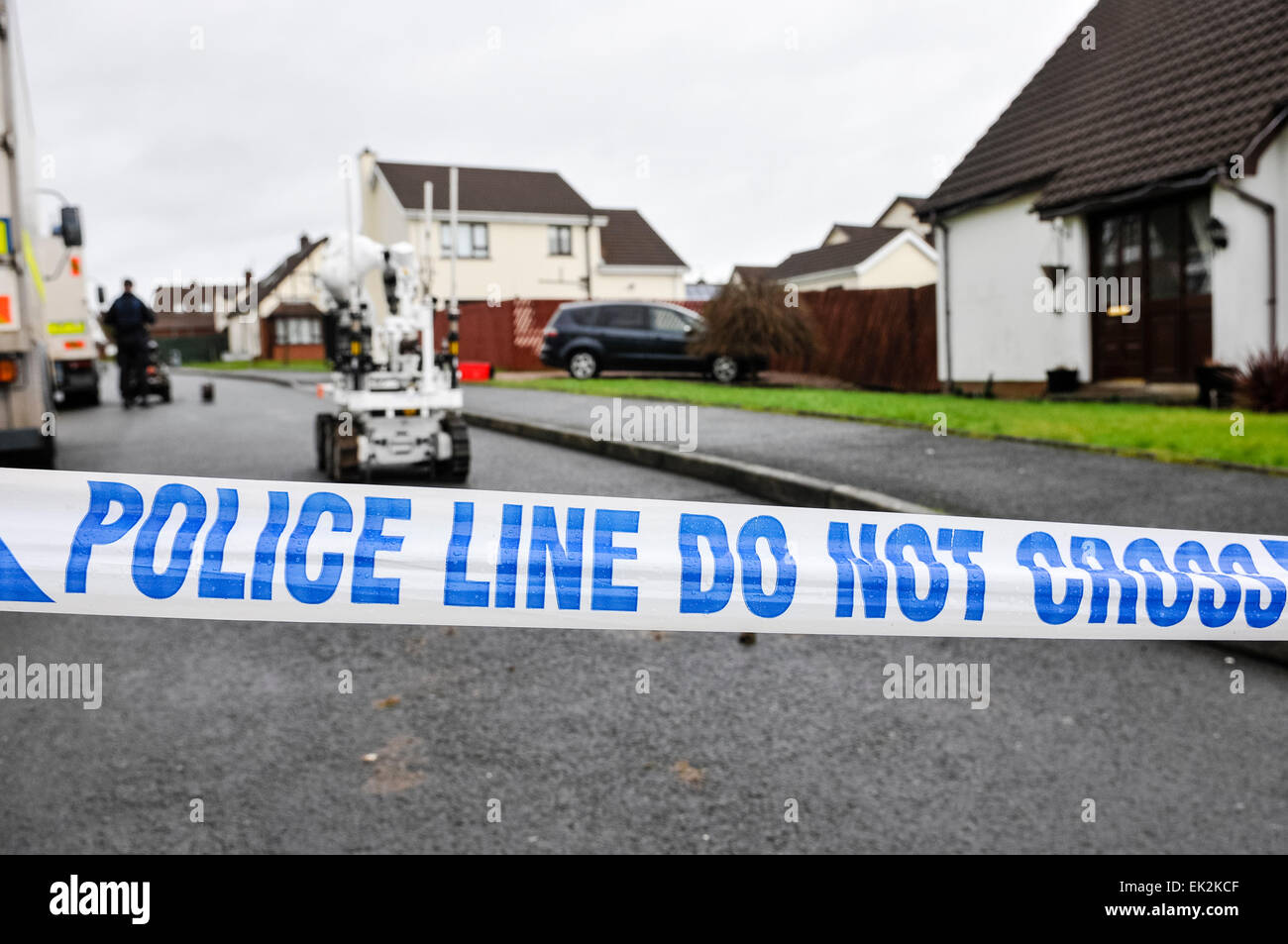 Police tape closes off a residential street as army ATOs use a robot to make safe a suspicious device - Stock Image