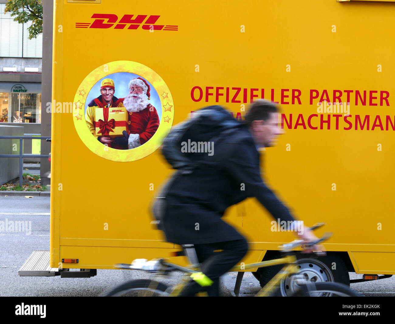 Germany Munich DHL deliver Truck n Bicycle commuter passing - Stock Image