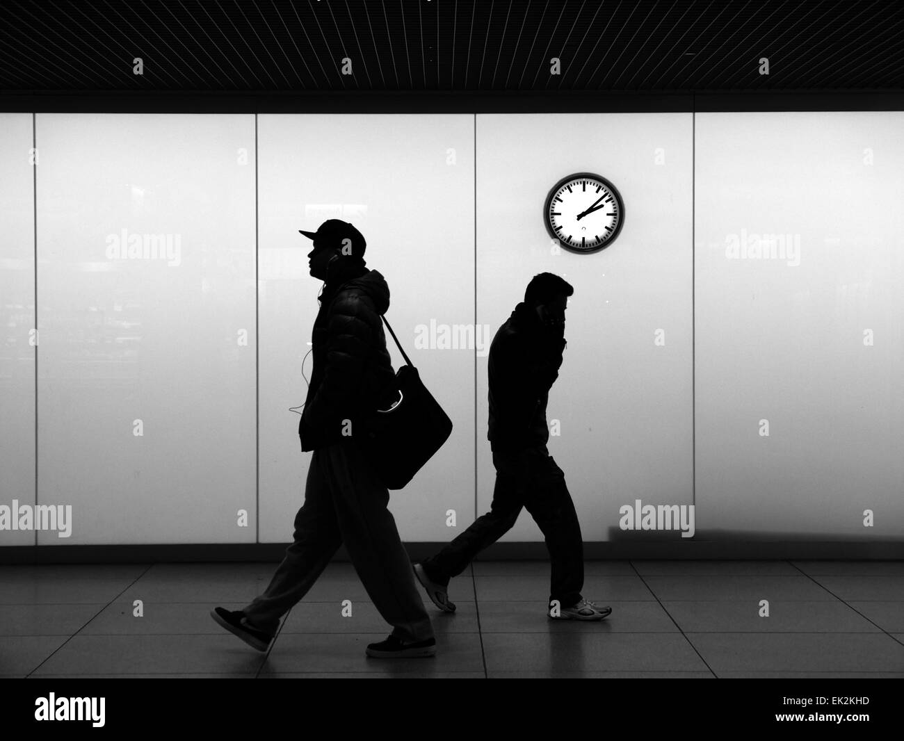 Urban City Commuters hurry commuting under wall clock. Modern commuters listening music or talking with smartphone - Stock Image