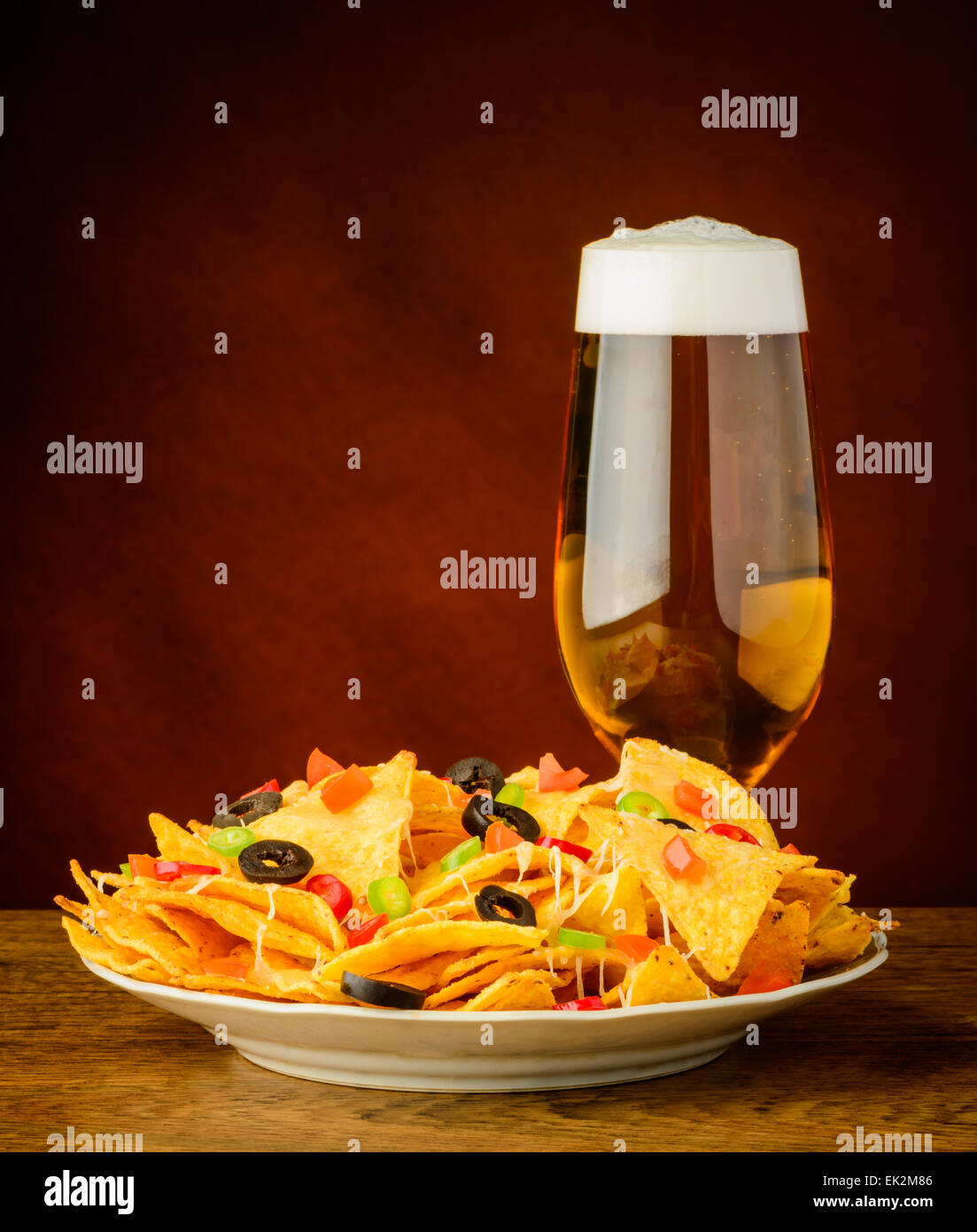 baked tortilla chips with cheese, olives and chili peppers and glass of beer Stock Photo
