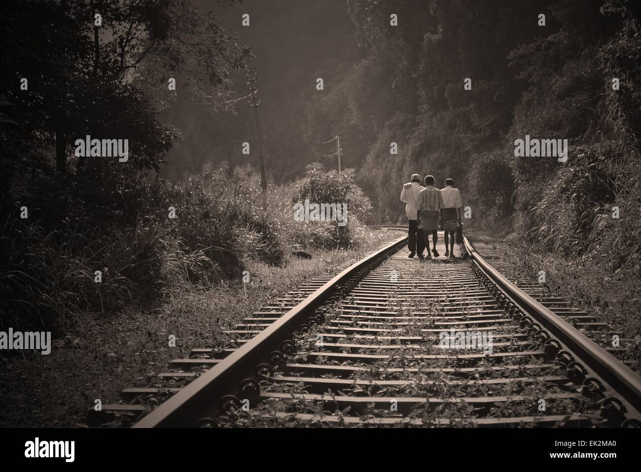 Kids at a distance walking on old railway tracks - Stock Image