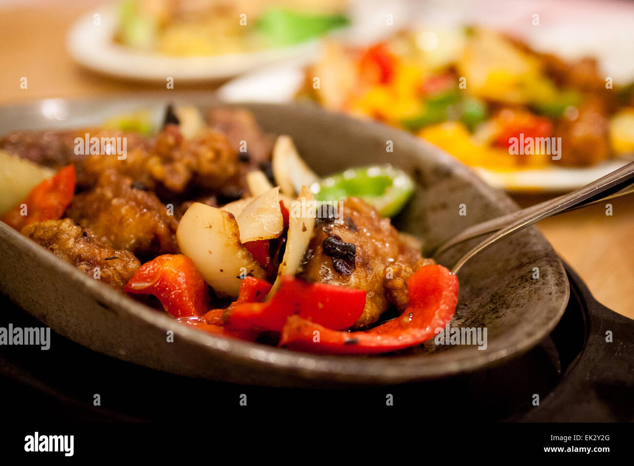 Chinese food: stir fry chicken and vegetables in a black bean sauce, served on a hot, cast iron plate. - Stock Image
