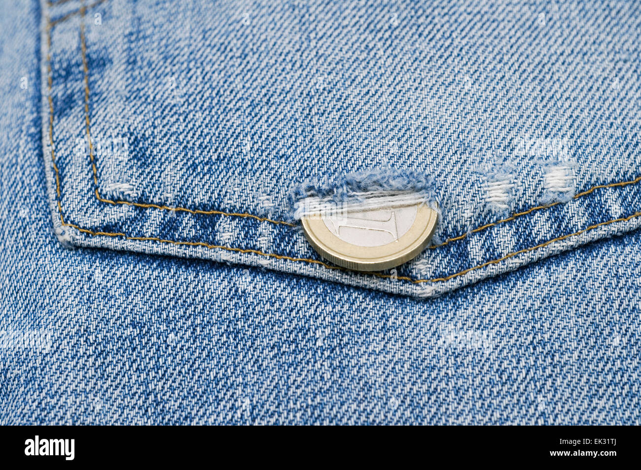 Euro coin Slipping Through A Hole On The Pocket Of Blue Jeans - Stock Image