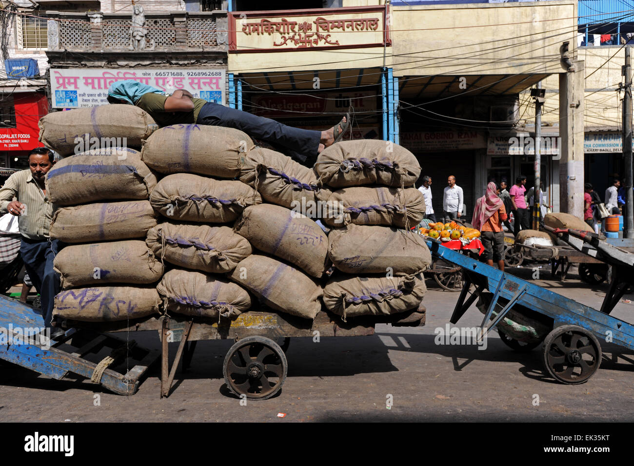 Worker sleeping over a pile of sacks of rice in the middle of a busy market in Delhi,India - Stock Image