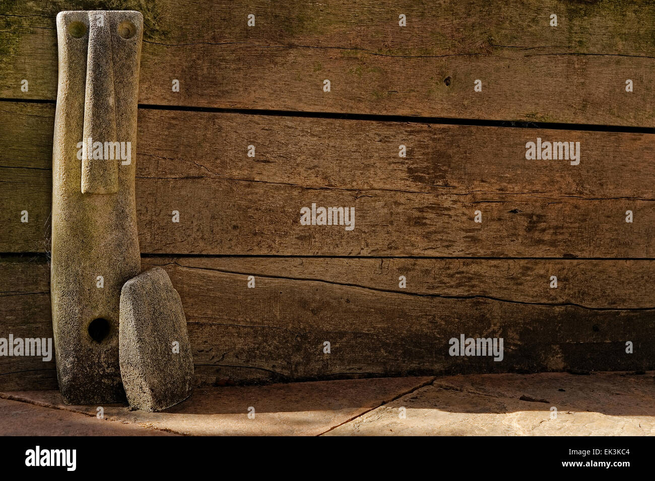 Concrete statue of stylized elongated face and hand against weathered wooden fence. - Stock Image