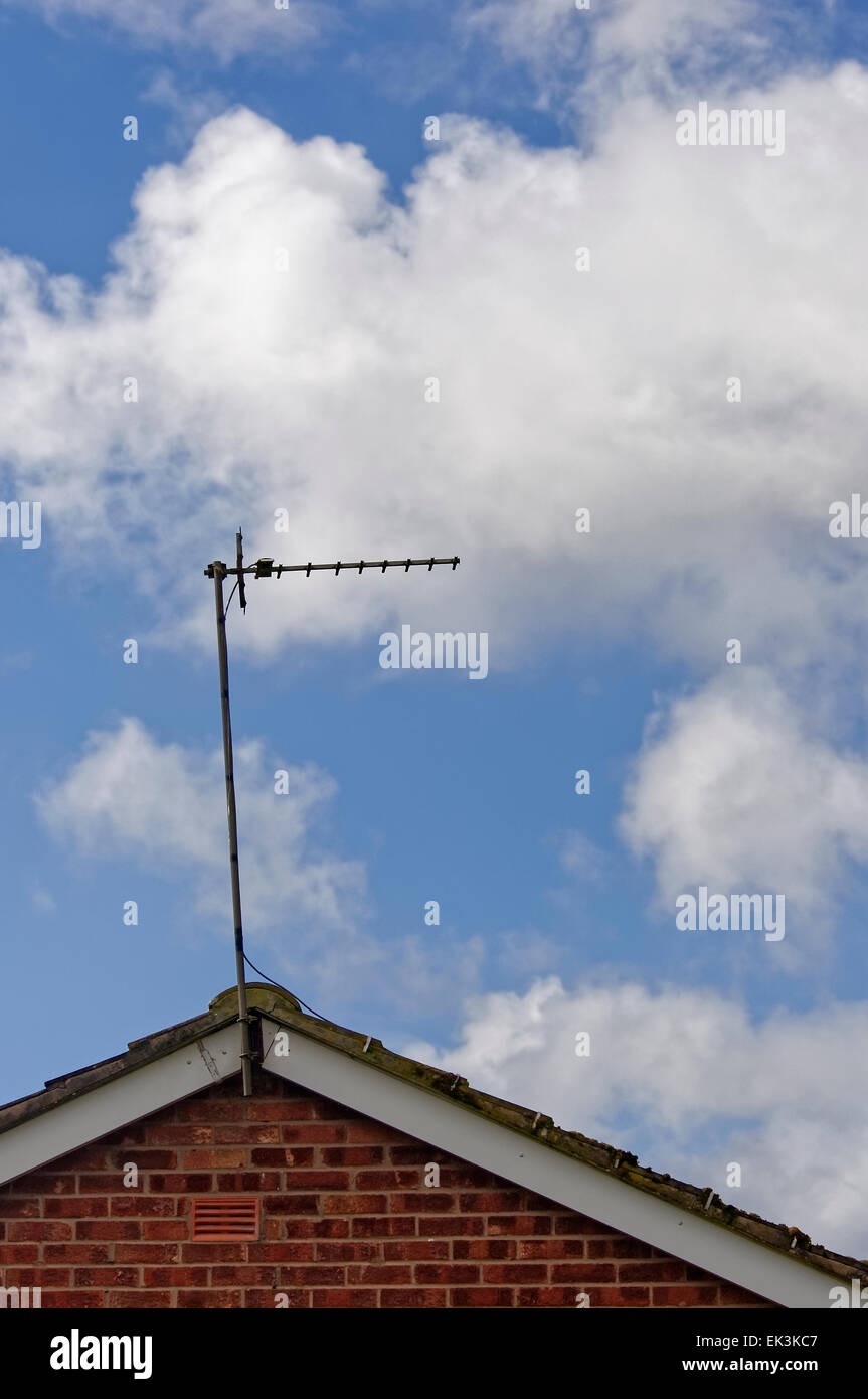 Basic television aerial / antenna on roof of house against blue sky with white clouds. - Stock Image