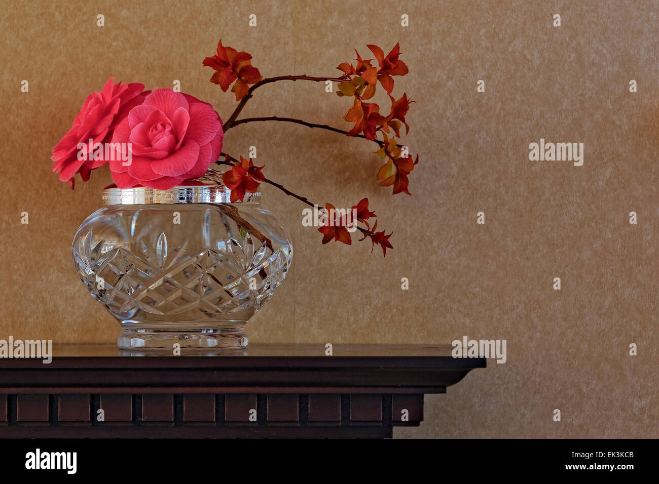 Flower Arrangement Including Camellia Flowers In Crystal Vase On Carved Wooden Mantelpiece Against Plain Wallpaper