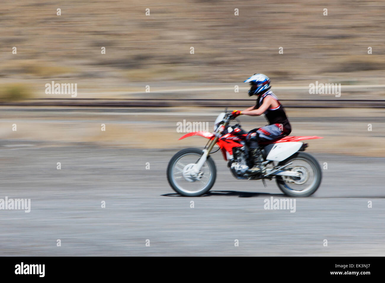 Man riding a dirt bike, motorcylce, on the barren land along Arkansas River owned by Union Pacific Railroad. - Stock Image