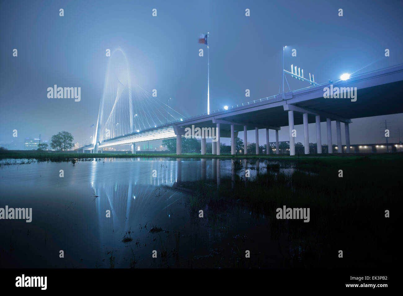 Wide long exposure shot of Margaret Hunt Hill Bridge in downtown Dallas Texas on a misty foggy night with a reflection. - Stock Image