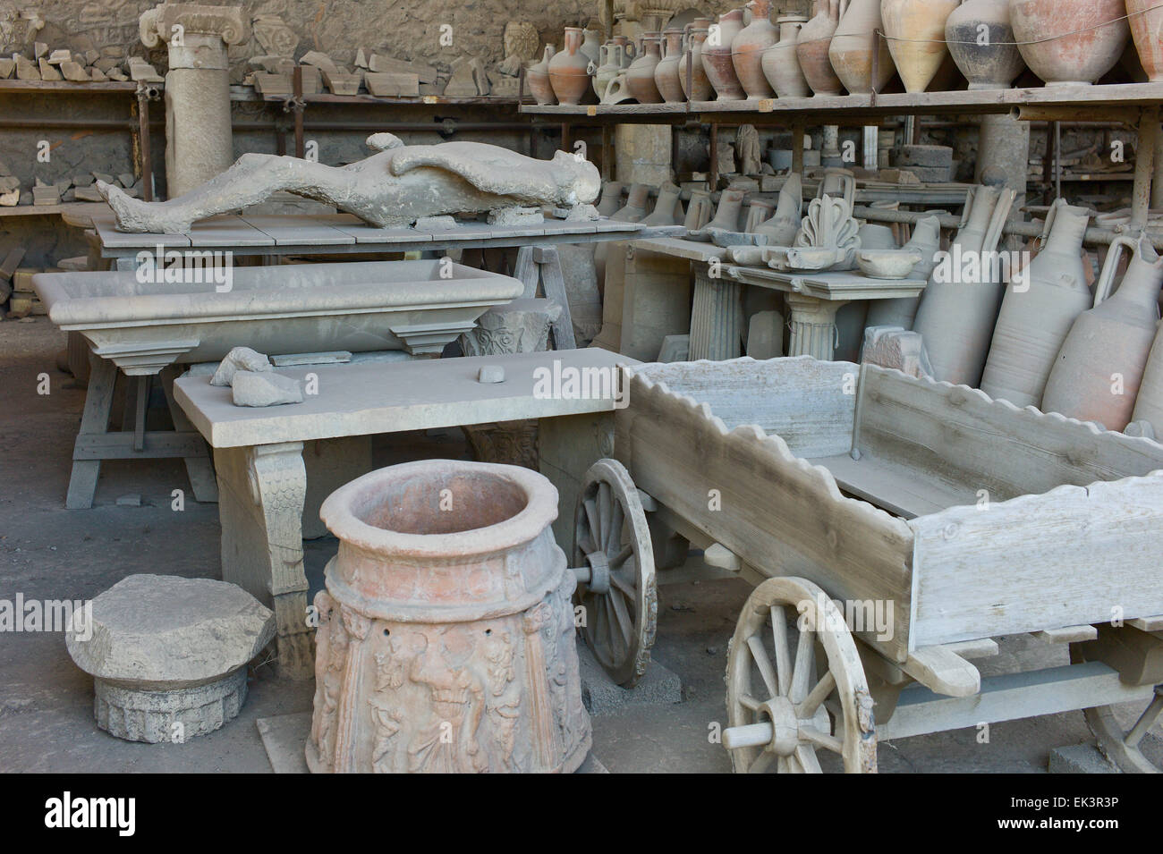 Storage of artefacts including a plaster cast of human remains and amphora pots in Pompei, Italy - Stock Image