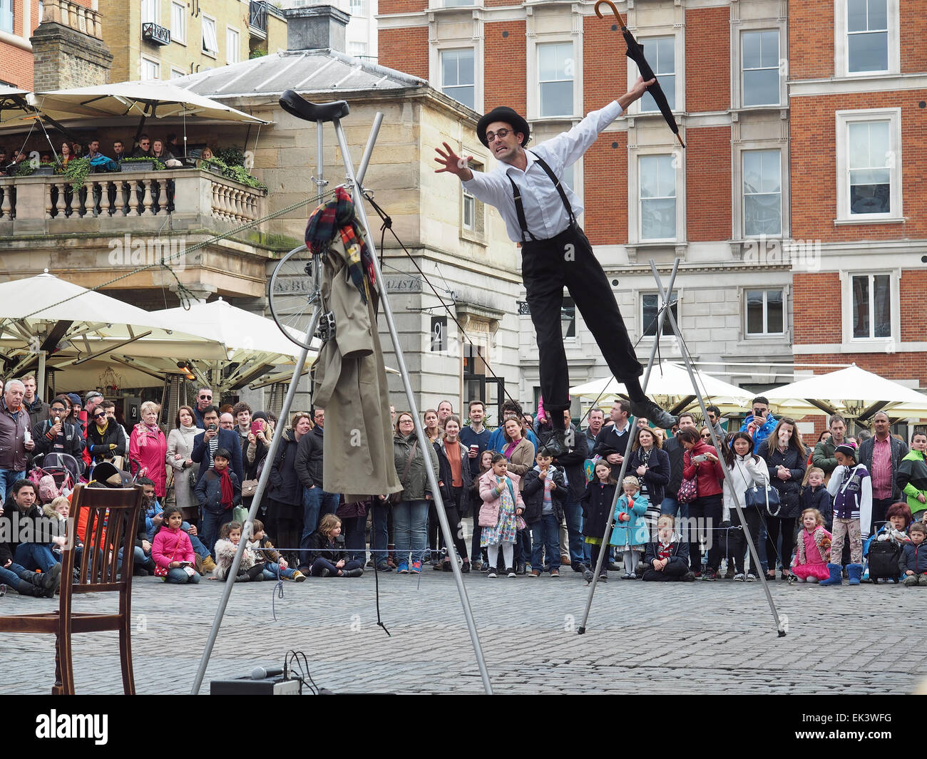 A tightrope walker entertaining a crowd in Covent Garden London UK - Stock Image