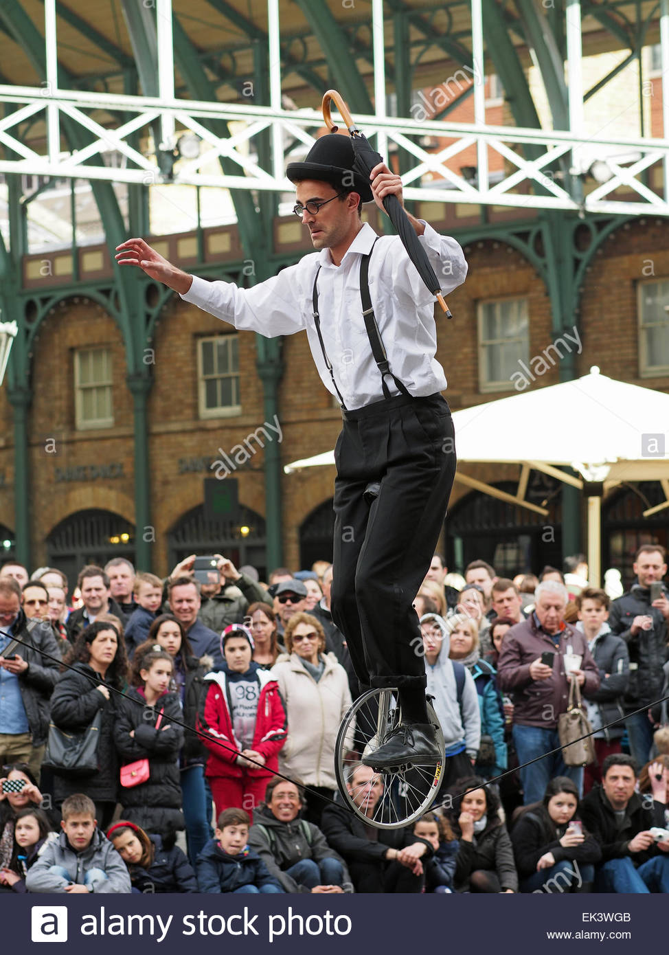 A tightrope walker on a unicycle entertaining a crowd in Covent Garden London UK Stock Photo