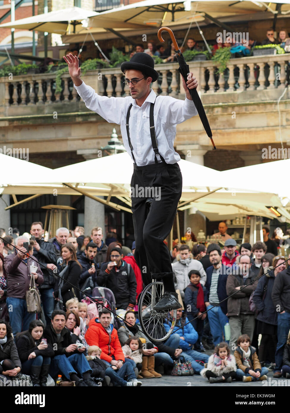 A tightrope walker on a unicycle entertaining a crowd in Covent Garden London UK - Stock Image