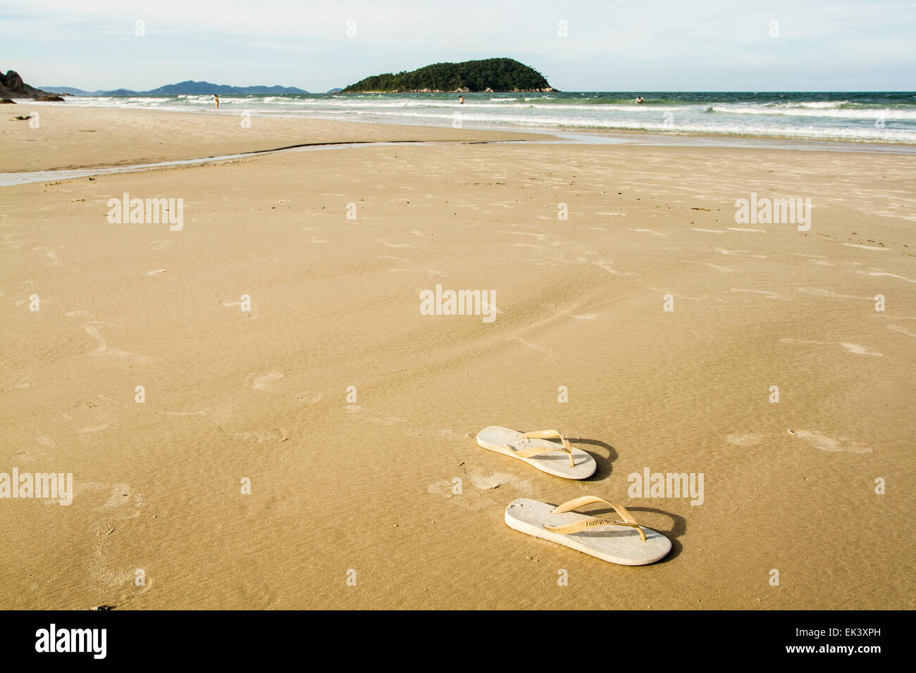 Flip flop sandals on the sand at Palmas Beach. Governador Celso Ramos, Santa Catarina, Brazil. - Stock Image