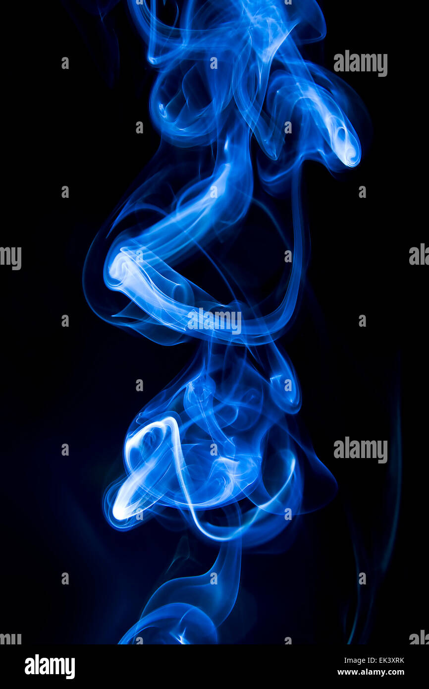 Curling blue smoke rings on black background - Stock Image