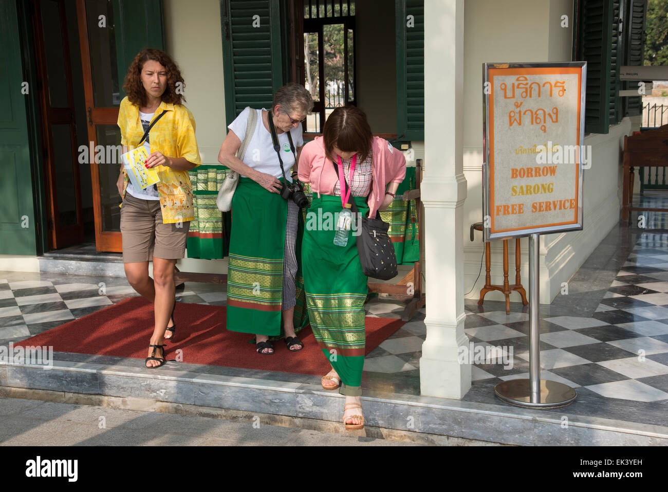 Tourists borrow a sarong before entering a religious temple Thailand as a mark of respect the legs are covered before - Stock Image