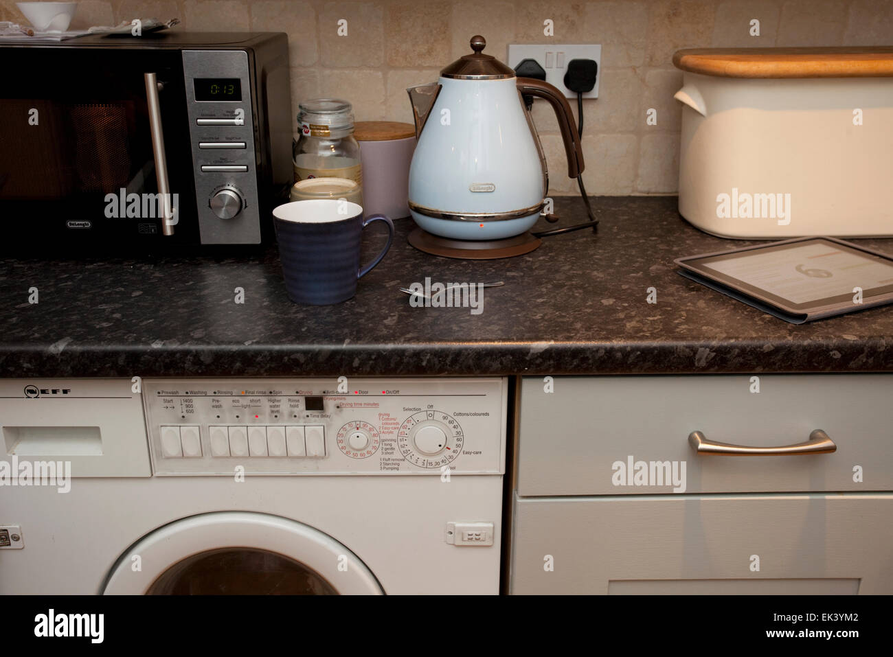 All appliances on kitchen worktop being used at once Stock Photo