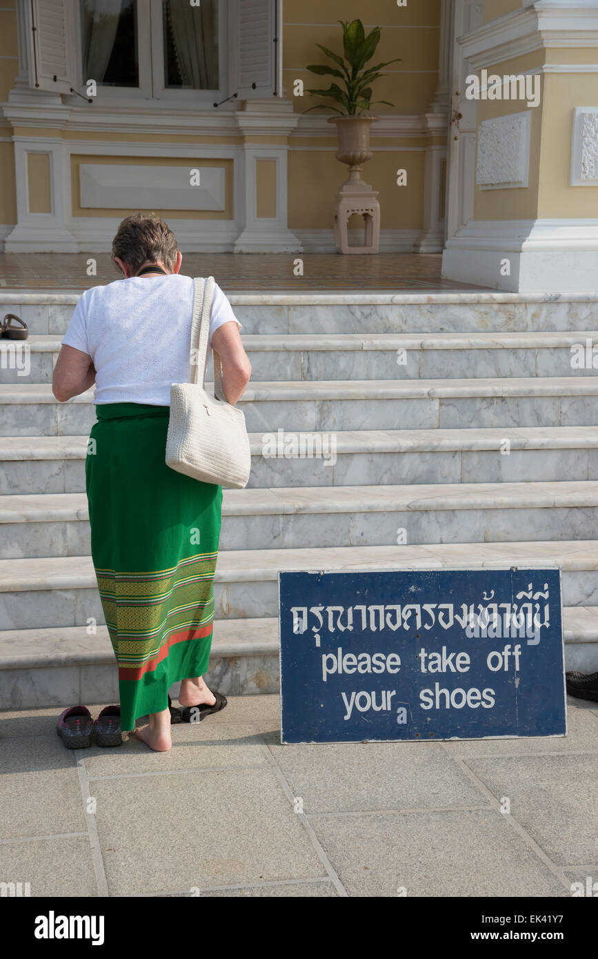 Please remove shoes notice at a Thai temple in Ayutthaya Thailand. Tourist removing her footwear - Stock Image