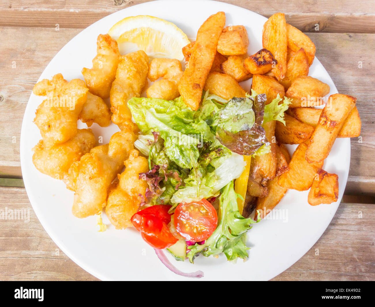 A simple pub lunch of breaded Scampi with lemon, salad garnish and chips - Stock Image