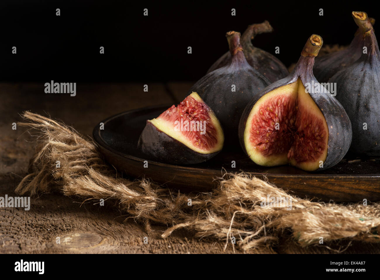 Fresh figs in moody natural lighting set with vintage style - Stock Image