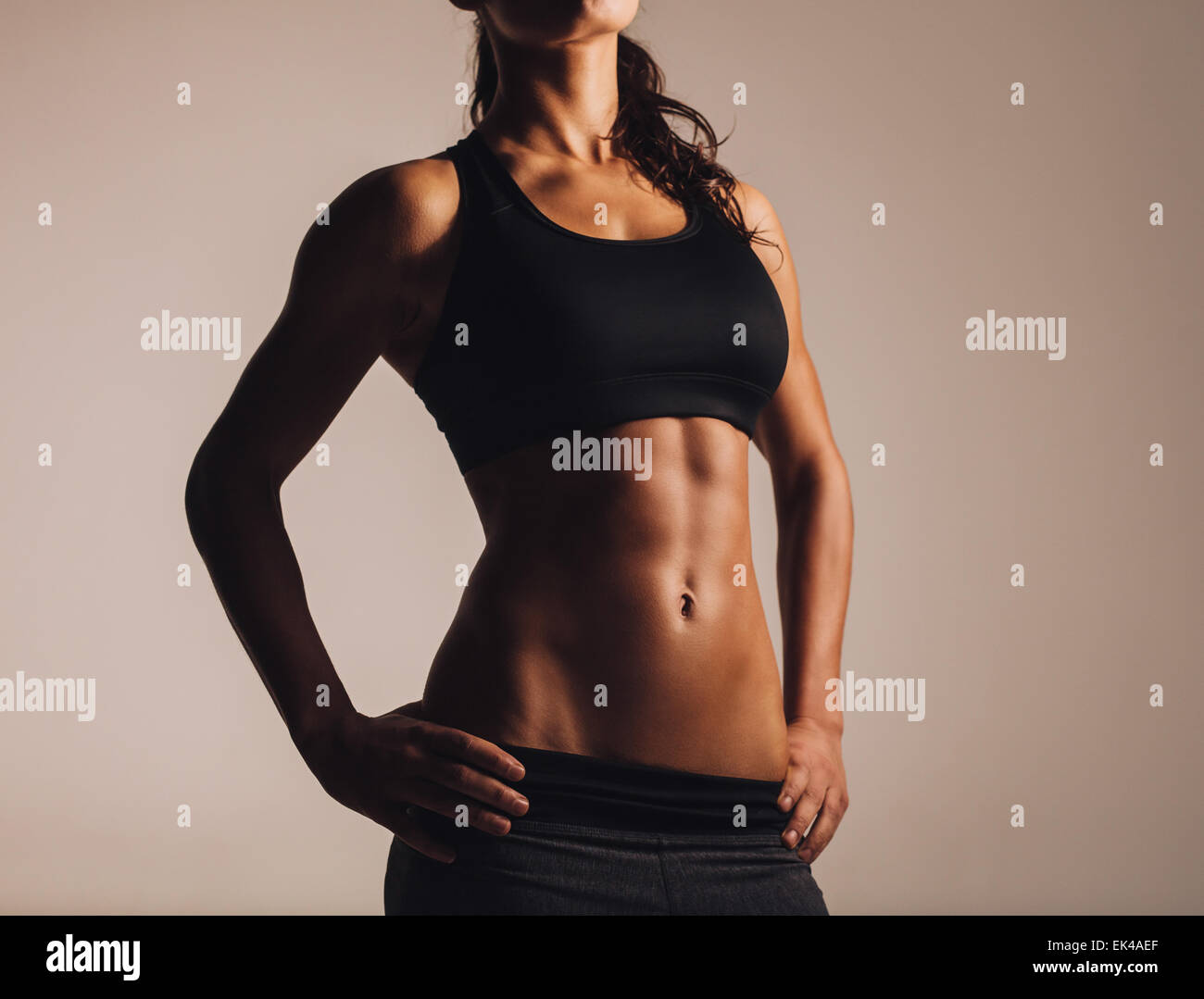 Fitness female model torso with her hands on hips. Female with perfect abdomen muscles. - Stock Image
