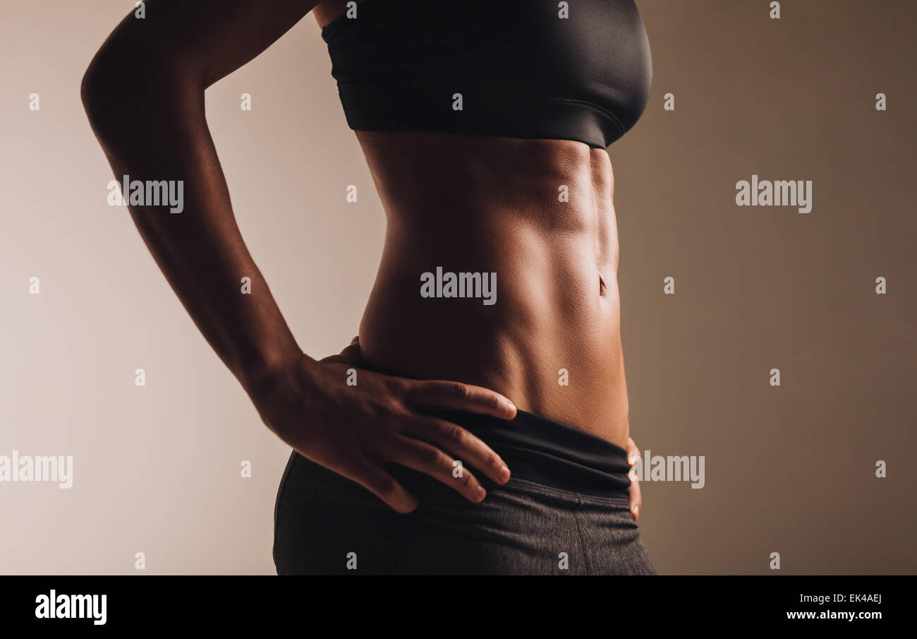 Cropped image of woman's waist. Perfect abdominal muscles of fit female model. - Stock Image
