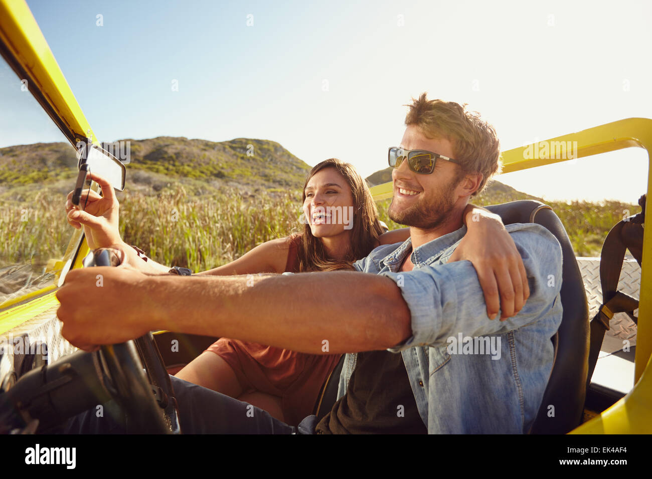 Man driving beach buggy with woman taking selfie on her smart phone. Couple having fun on road trip on a summer - Stock Image