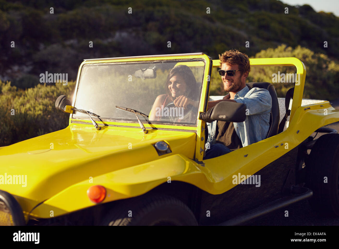 Shot of a handsome young man driving a buggy car in the countryside with his girlfriend. Cheerful young couple on Stock Photo