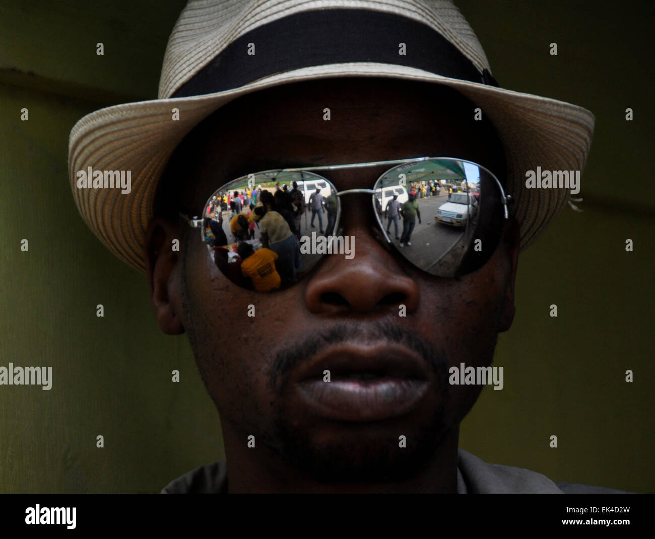 Voters reflected in the glasses of Siya, a man sitting near the voting station in Imizamo Yethu, an informal settlement, Stock Photo