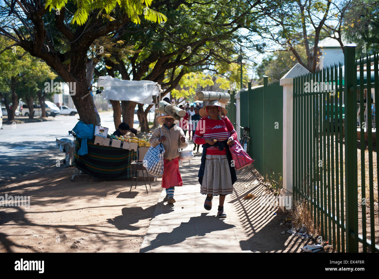 women walking on the street carrying traditional woven mats made from grass . a statue of cecil john rhodes was - Stock Image