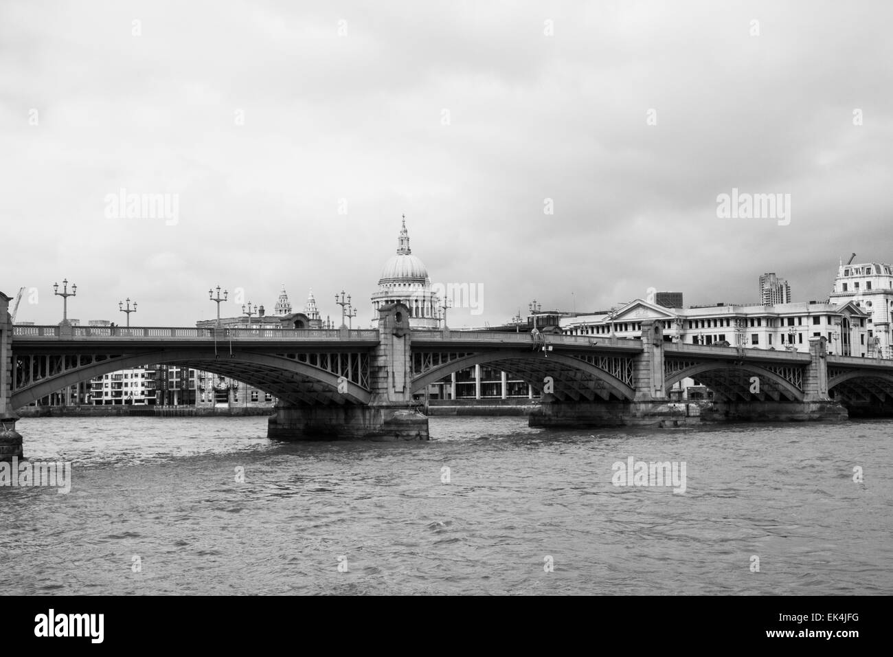Black & white of St Paul's Cathedral from the South Bank with the Thames and Southwark Bridge in the foreground - Stock Image