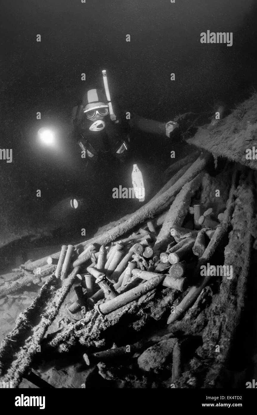 Montenegro, Adriatic Sea, U.W. photo, wreck diving, diver and cannon bullets in a sunken ship - FILM SCAN - Stock Image