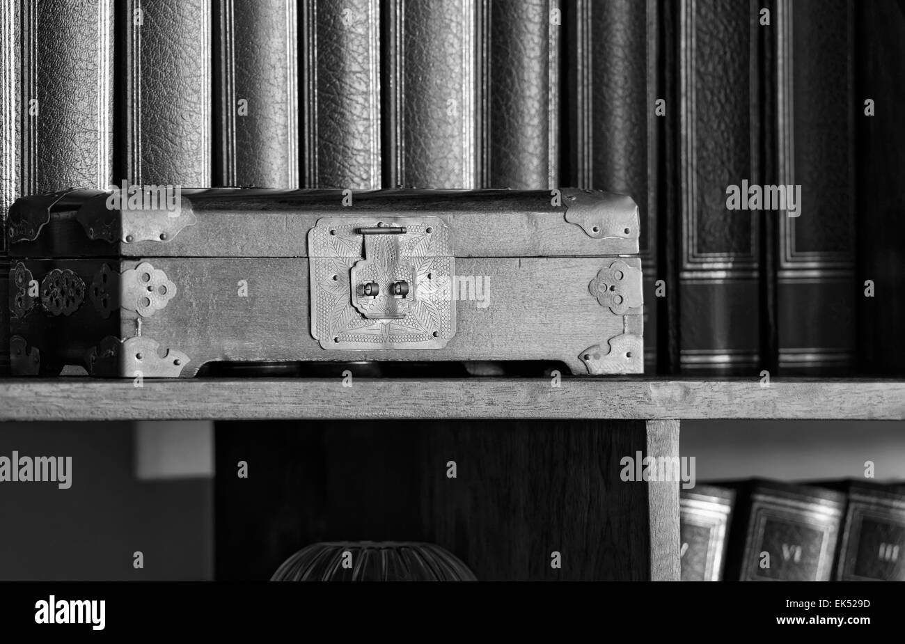 Old oriental hand made wooden box in a library - Stock Image