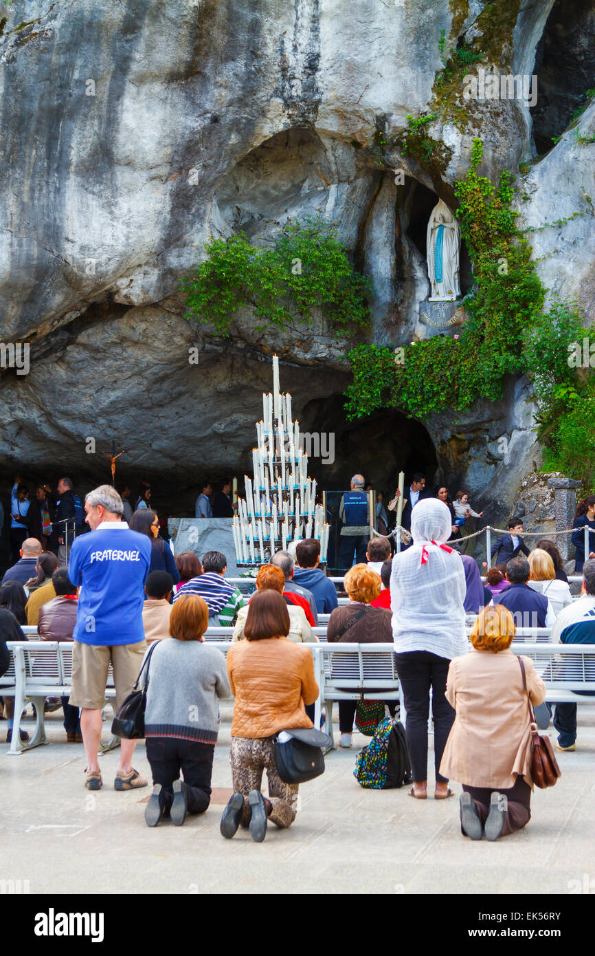 Massabielle grotto, statue of Our Lady of Lourdes and pilgrims. Lourdes city.  Midi-Pyrenees region, France, Europe. Stock Photo