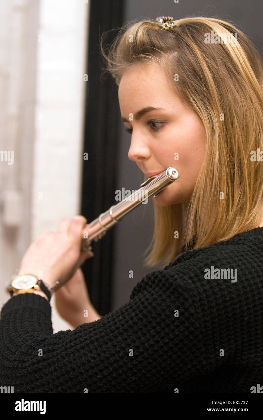Female music college student playing the Flute at a charitable music concert to support aspiring musicians and composers, - Stock Image
