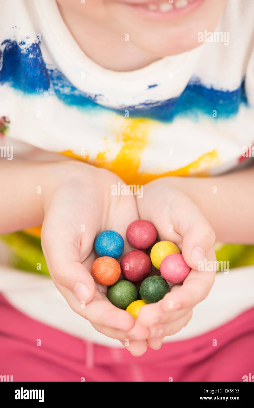 Little girl (5 years) holding colorful toy marbles in her hands. A moment of childhood fun and leisure games. - Stock Image