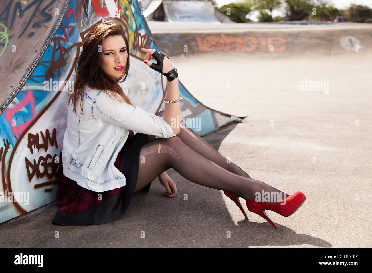 Young woman model sitting by graffiti wears punk inspired clothing with attitude in a skate park - Stock Image