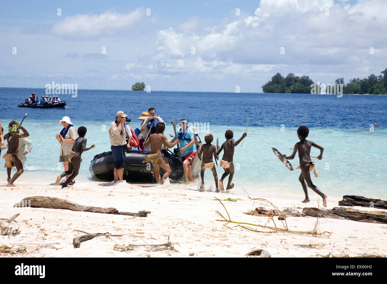 A group of young 'warriors' perform the customary welcome attack on cruise passengers getting out of a Zodiac - Stock Image