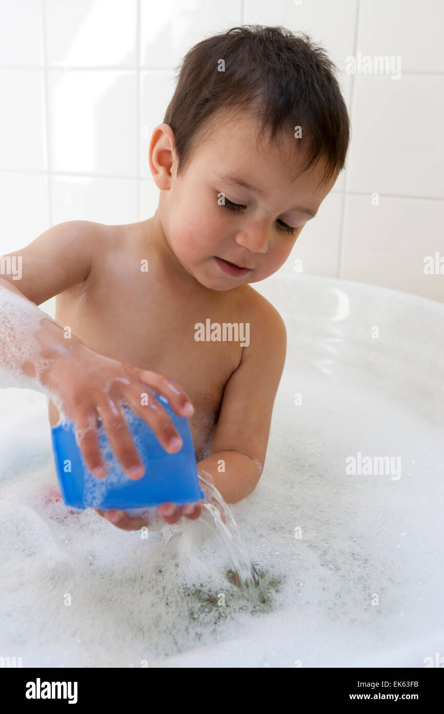 Two year old boy playing in the bath tub with water Stock Photo ...