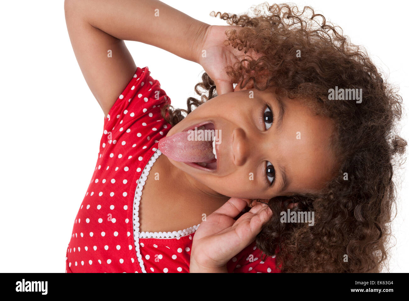Portrait of a five year old girl making faces and sticking out her tongue on white background Stock Photo